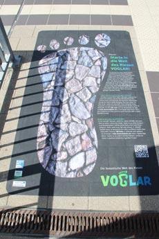 """Fußabdrücke des Riesen """"Voglar"""" weisen auf die Elstertalbahn hin. Darauf finden sich Hinweise auf Deutsch, Tschechisch und Englisch und ein QR-Code; Foto: Gunther Brand"""